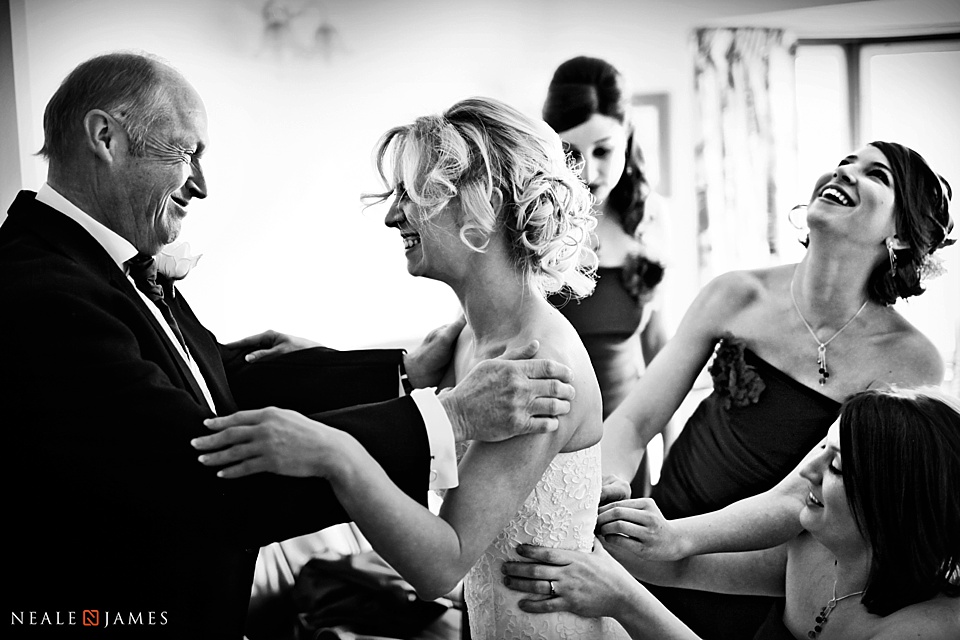 Bride with her father hugging in black and white photo