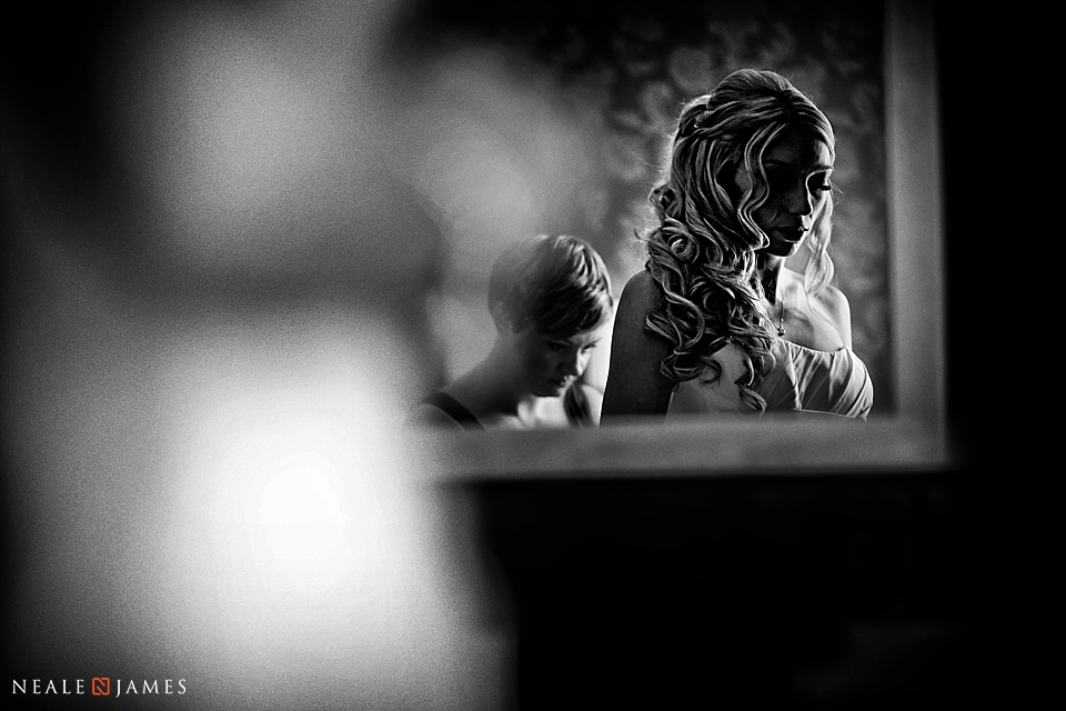 Black and white photograph of bride preparing for wedding